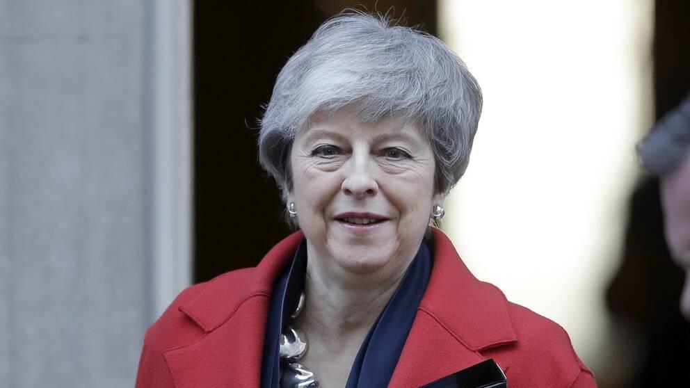 Theresa May i röd kappa.