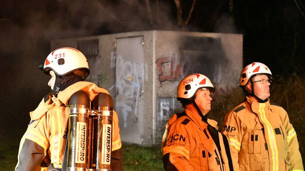 Tre brandmän och en rykande transformatorstation.