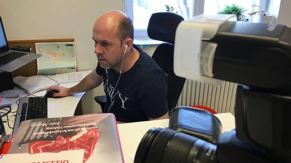 en man vid dator på ett kontor, kamera och bok i förgrunden, en karta på väggen