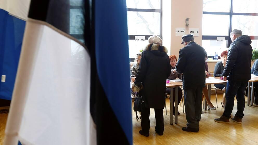 En kvinna och två män registrerar sig för att rösta i Estlands parlamentsval. Estlands flagga i förgrunden.