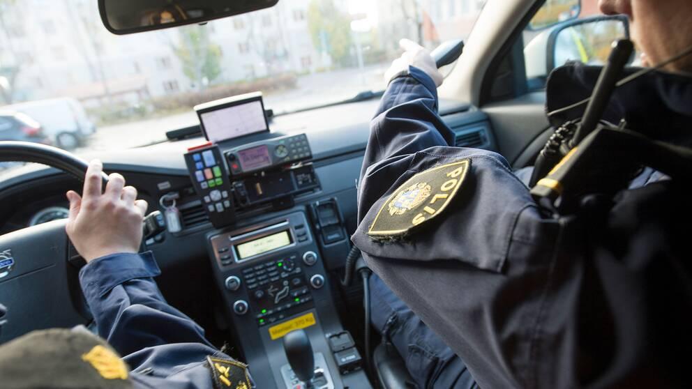 Två poliser i en polisbil.