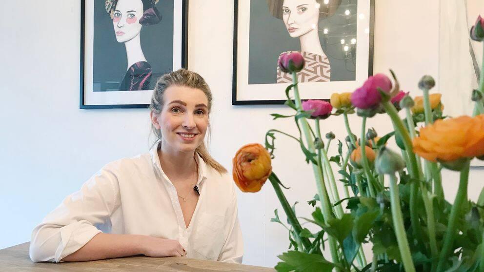 Charlotte Peel i vit skjorta sitter framför två av sina tavlor, två vackra kvinnor som stirrar över ena axeln rakt in i betraktarens ögon. I förgrunden på bilden syns ett stort fång orangea och rosa ranunkler i en vas.