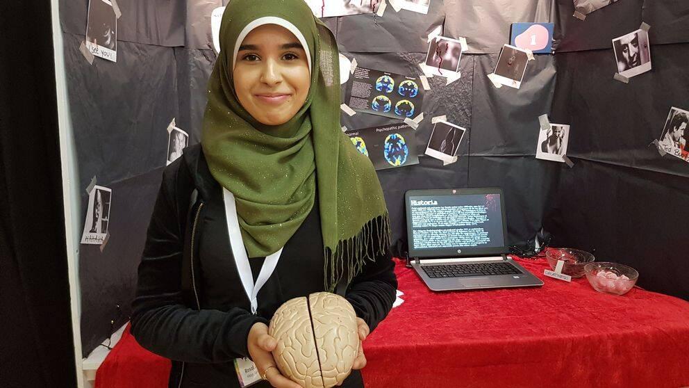 En ung tjej står vid sin monter och håller i en modell av en hjärna.