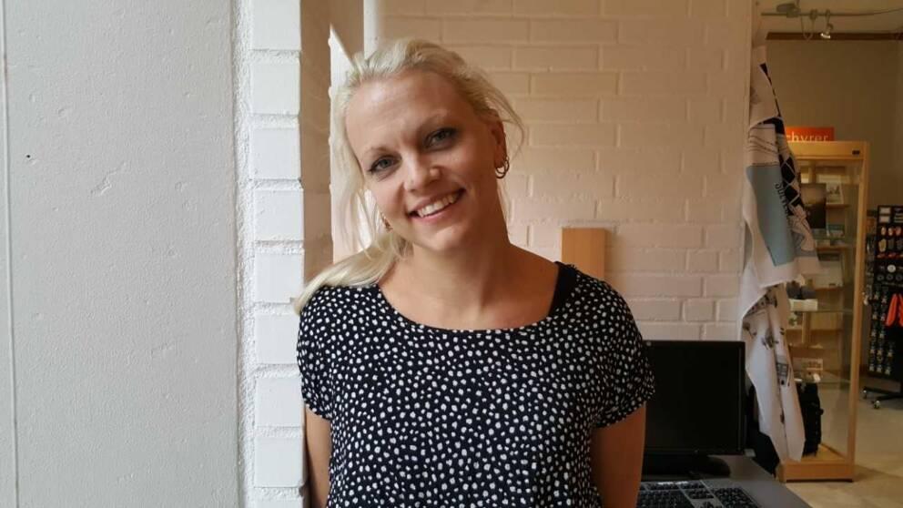 blond kvinna i prickig tröja ler