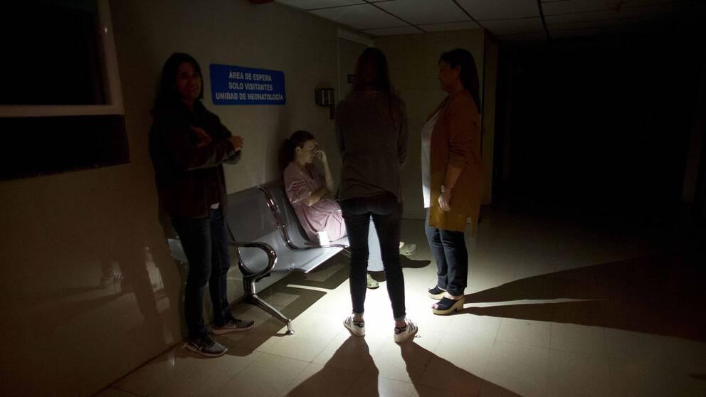 Anhöriga väntar i en strömlös korridor vid en intensivvårdsavdelning för spädbarn i Caracas under strömavbrottet.
