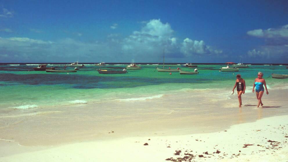 Två kvinnor går på en strand på Barbados.