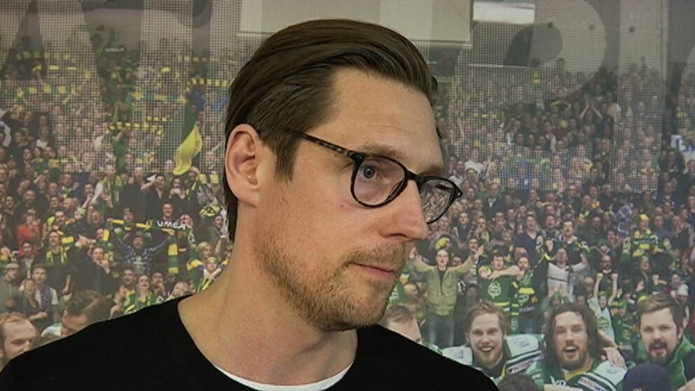 en man med brunt hår och rundade svartmelerade glasögon