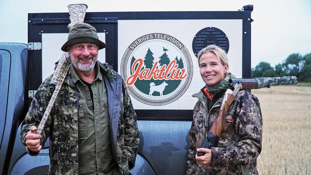 """en man och en kvinna i kamouflagekläder med bössor på axeln står på en åker framför en bild med skylt: """"Jaktliv"""""""