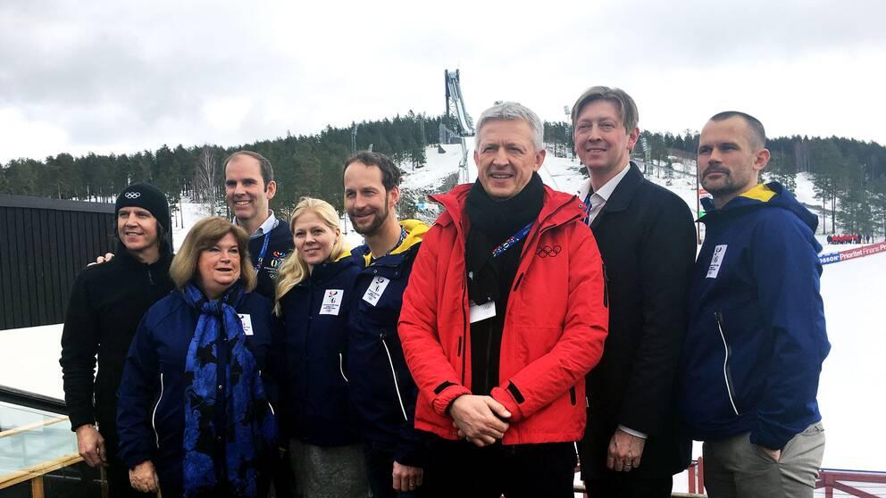 Flera personer står i en klunga och tittar in i kameran. I bakgrunden ses snöiga hoppbackar.