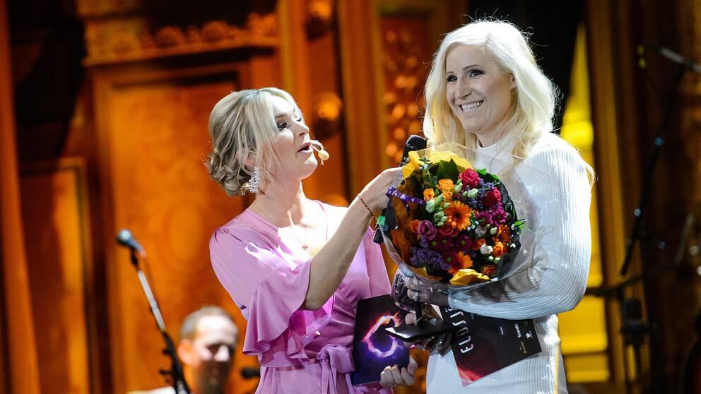 två festklädda kvinnor med blombukett på en scen