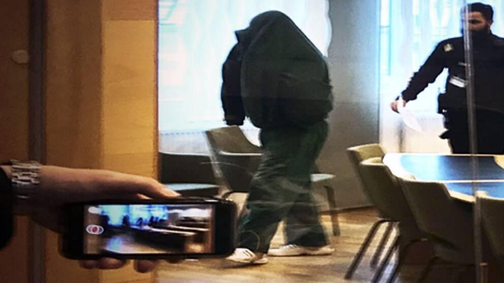 Styckmordet i Västerås. Misstänkt mördare döljer sitt ansikte i rättssalen vid Västmanlands tingsrätt.