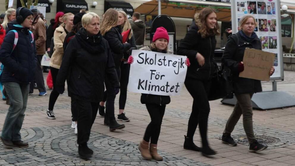 flicka med rosa mössa håller i klimatstrejk-skylt