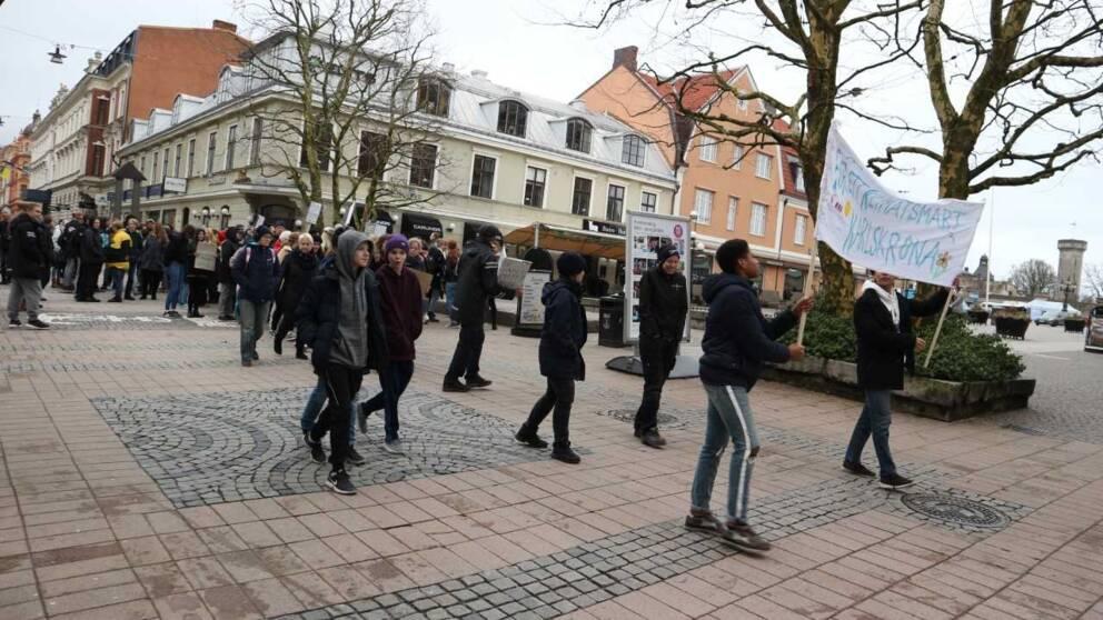unga bär banderoller på gågata