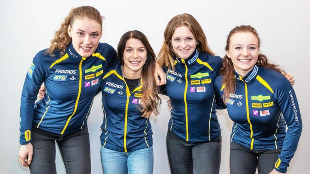 Hanna Öberg, Anna Magnusson, Mona Brorsson och Linn Persson står bredvid varandra och håller om varandra. De är iförda träningsjackor med de svenska färgerna.