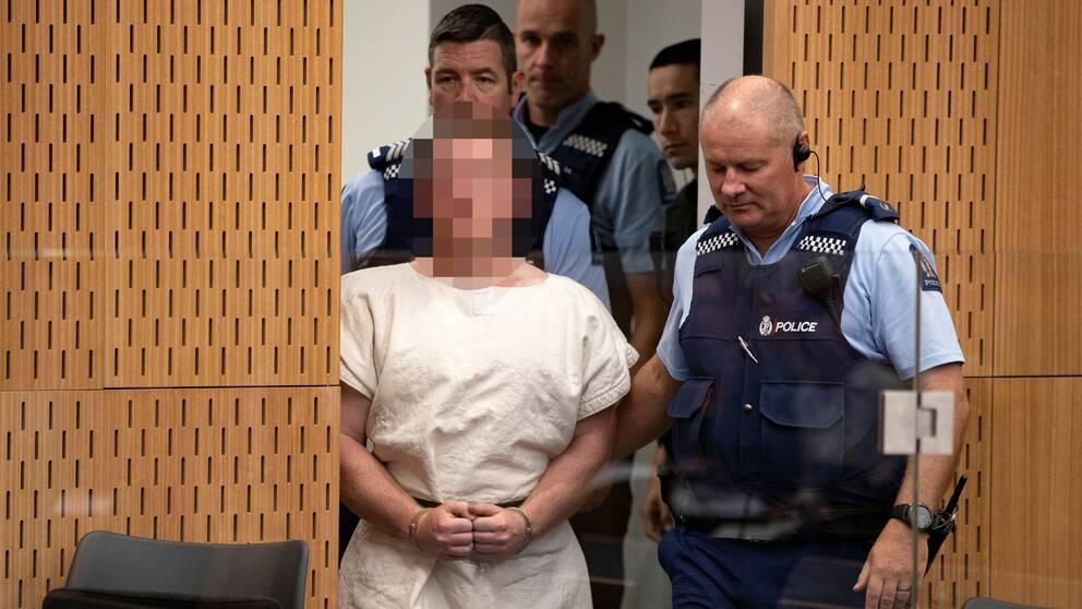Här förs Brenton Tarrant in i rättsalen. Domaren beordrade att alla bilder som togs på den misstänkte terroristen i rättsalen skulle pixlas.