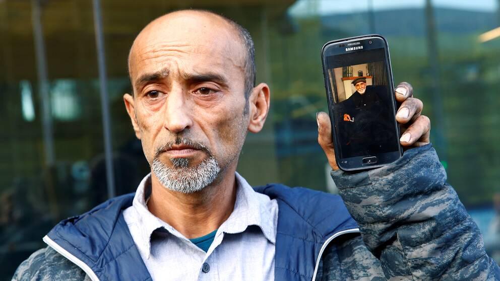 Sonen Omar Nabi visar upp en bild på sin pappa Daoud Nabi.