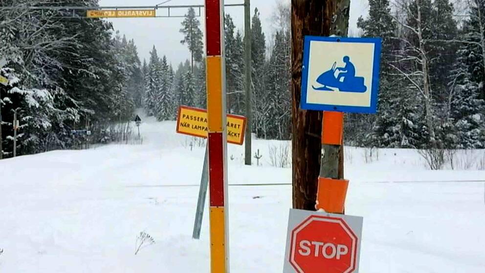En vinterväg korsar en tågövergång. En skylt för skoterled sitter på en stolpe.