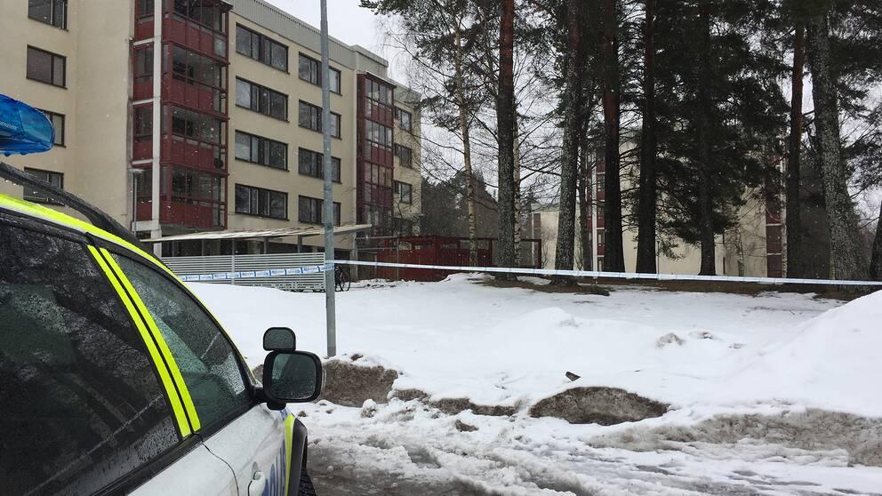 del av polisbil i förgrunden, snö på marken, polistejp, vy mot lägenshetshus