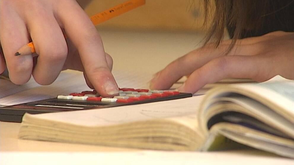 Elev pluggar matte med miniräknare.