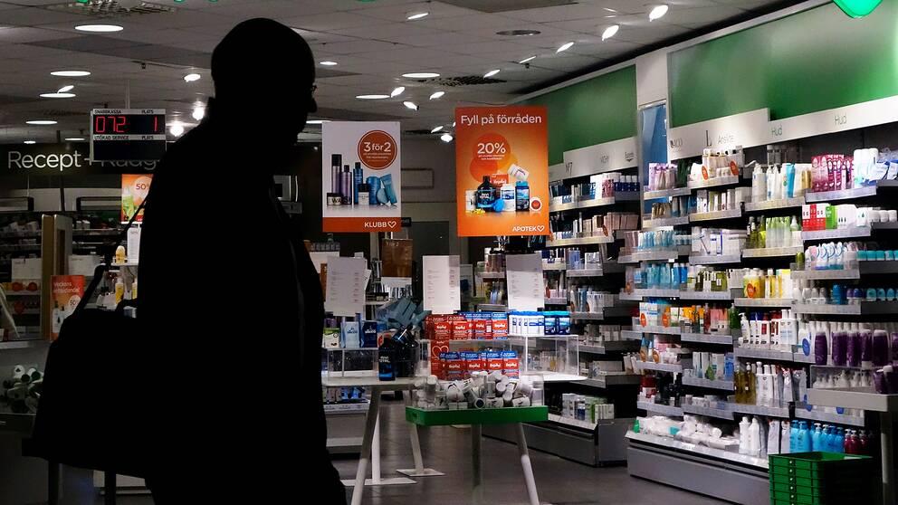 En man som går förbi ett apotek.