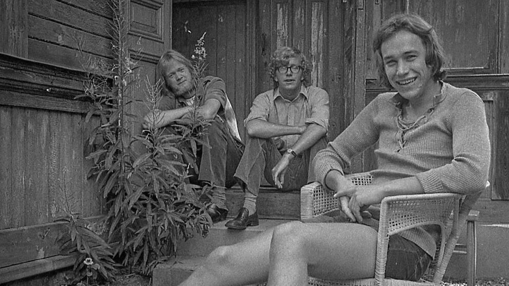 Tre män som sitter framför ett hus – svartvitt foto
