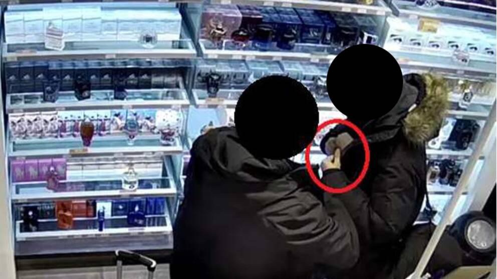 Två personer, vars ansikten har maskats, i färd med att stjäla parfym vid en hylla full med parfymflaskor.