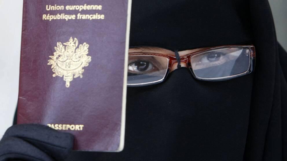 En fransk kvinna håller upp sitt pass under en presskonferens 2010, när lagen trädde i kraft.