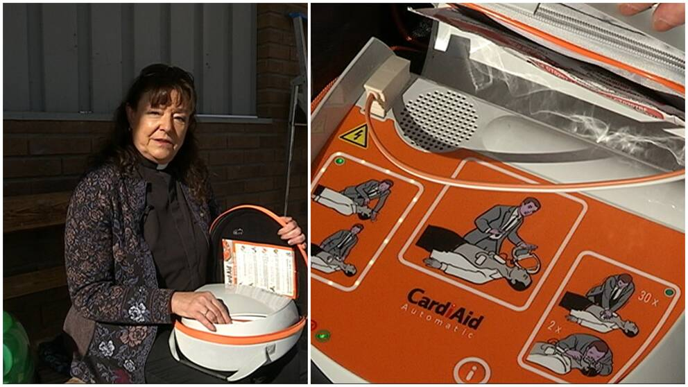 Kyrkoherde Monica Jones med en hjärtstartare i famnen. Inzoomning på manual med instruktioner.