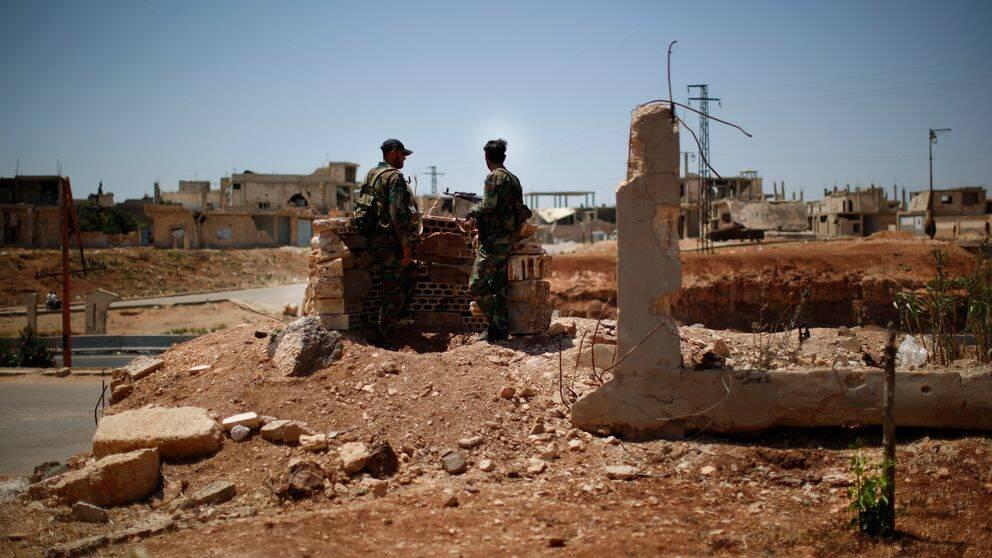 Två syriska soldater på en sandig kulle.