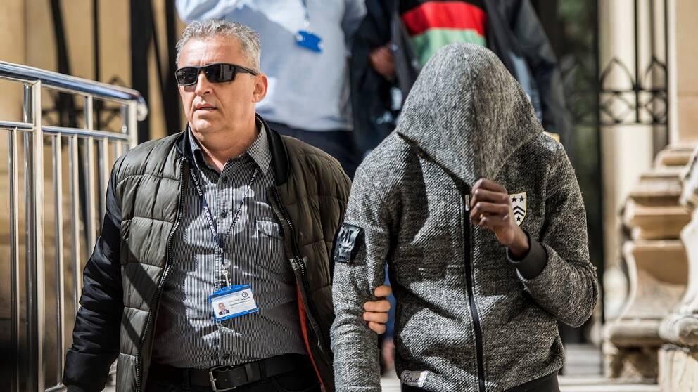 En av de anklagade tonåringarna förs ut från rätten i Valletta, Malta.