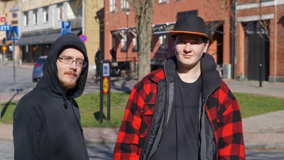 två yngre män klädd i huva och keps