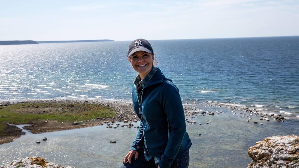 Kronprinsessan ler mot kameran på en strand, med keps på huvudet och horisonten i bakgrunden.