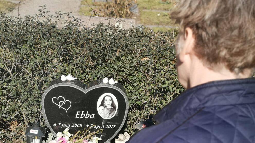 Stefan står framför dottern Ebba Stefansdotter Åkerlunds grav. Gravstenen pryds av en bild av Ebba.
