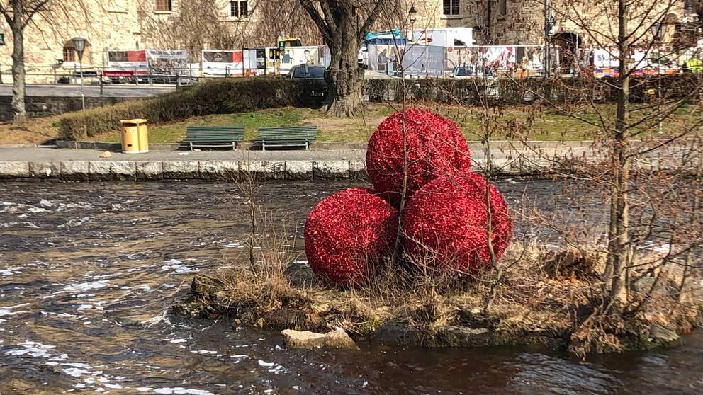 Tre röda julkulor ligger kvar i Svartån intill Örebro slott, trots att vi redan är inne i april.