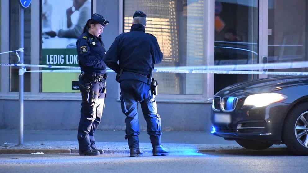 Två poliser och en bil som är avspärrad.