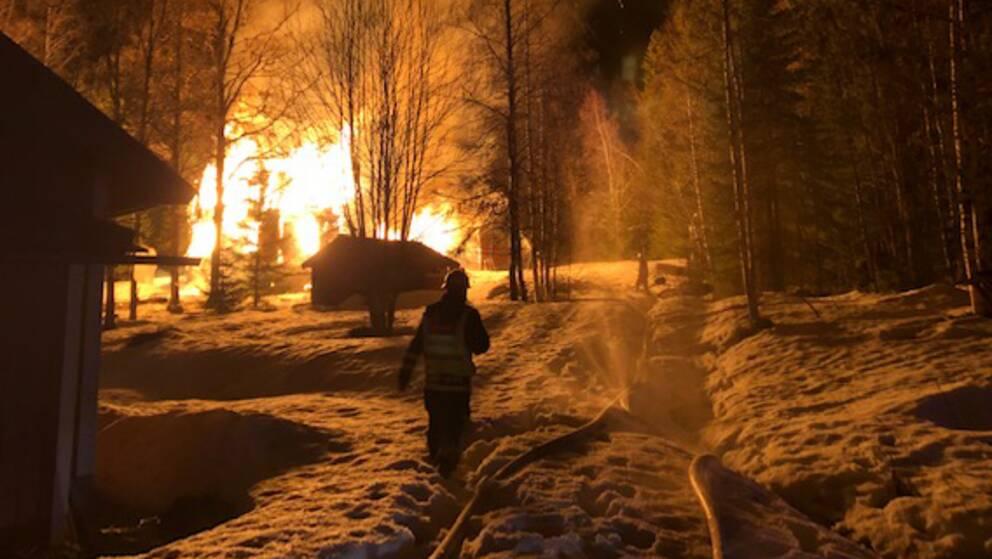 Brandman som går på väg med snö. Byggnad i brand en bit framför.