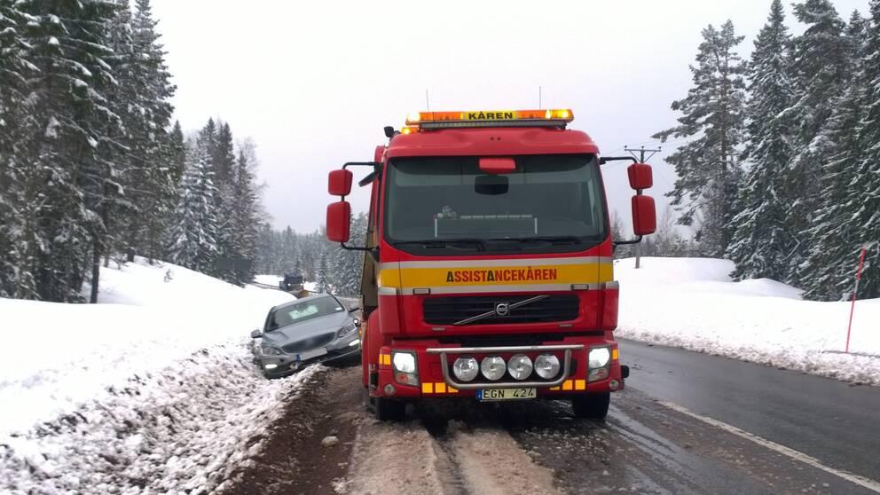 väg med snö och skog på sidorna, lastbil från Assistancekåren, bil som står på snedden halvvägs i diket, och långt bort ser man en plogbil komma