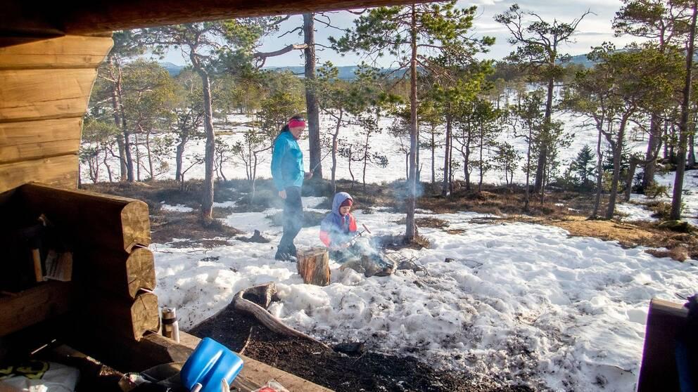 Kvinna och barn grillar korv i snön vid ett vindskydd