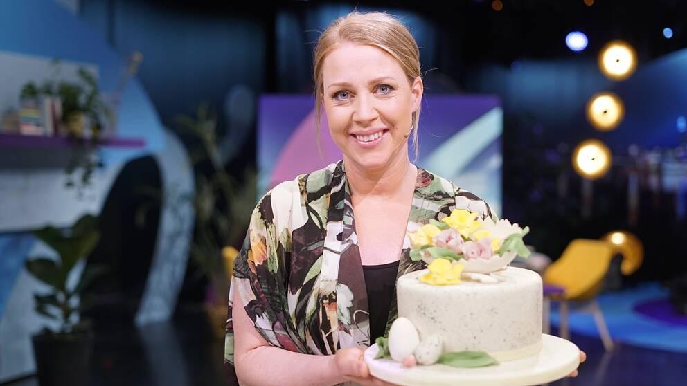 Tårtexperten Johanna Viberg håller en påskdekorerad tårta med sockerblommor.