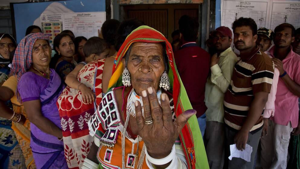 En kvinna visar upp bläcket på sitt finger efter att hon röstat.