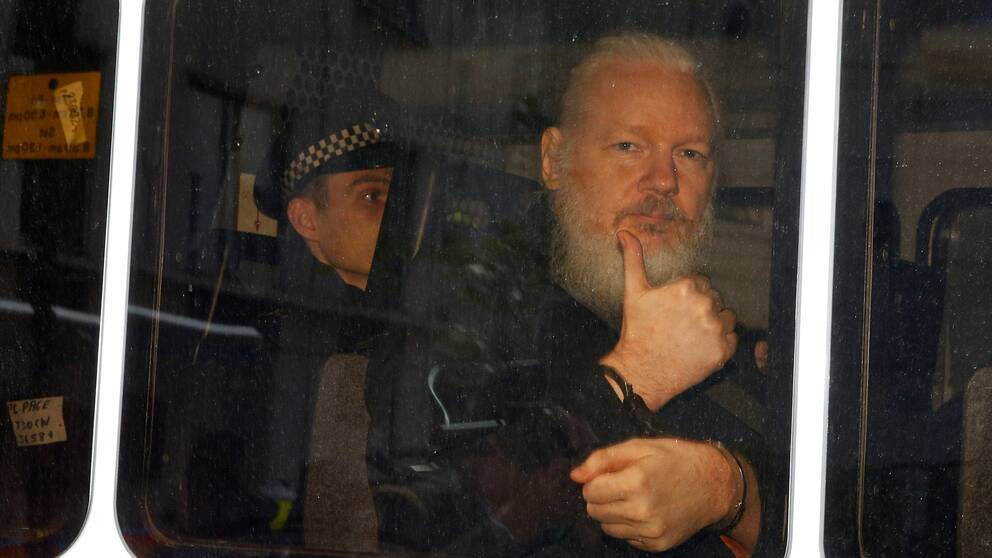 Julian Assange i en polisbil efter att han gripits av brittisk polis under torsdagen.
