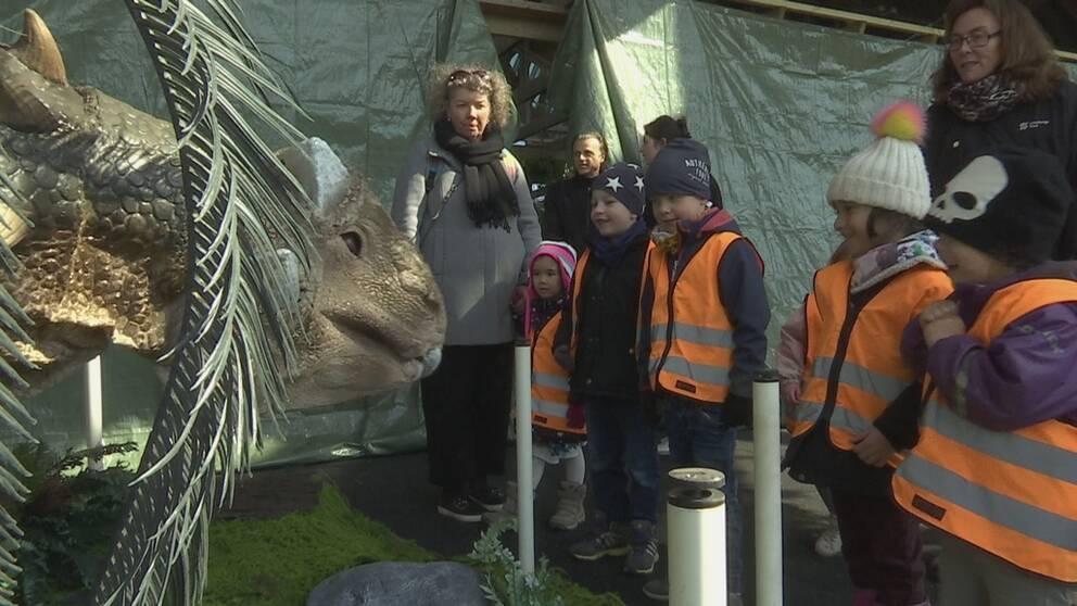 Flertal barn med två lärare och en dinosaurie.