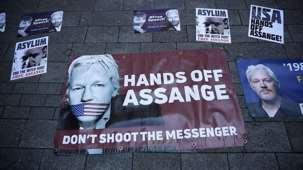 """Banderoller till stöd för Julian Assange med budskap som """"USA, rör inte Assange""""."""