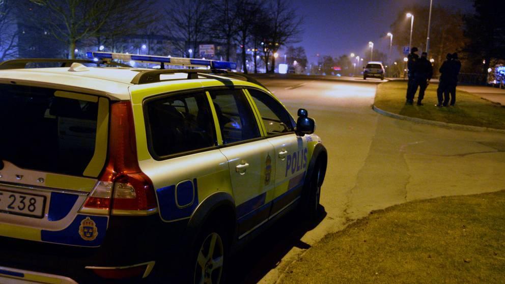 En polisbil i förgrunden och en grupp poliser längre bort, på natten. Bilden är från ett annat tillfälle.