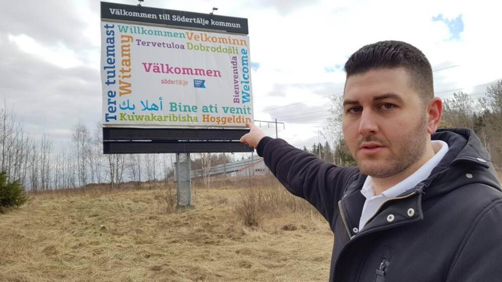 Aday Betkinne framför välkomstskylt vid infarten till Södertälje