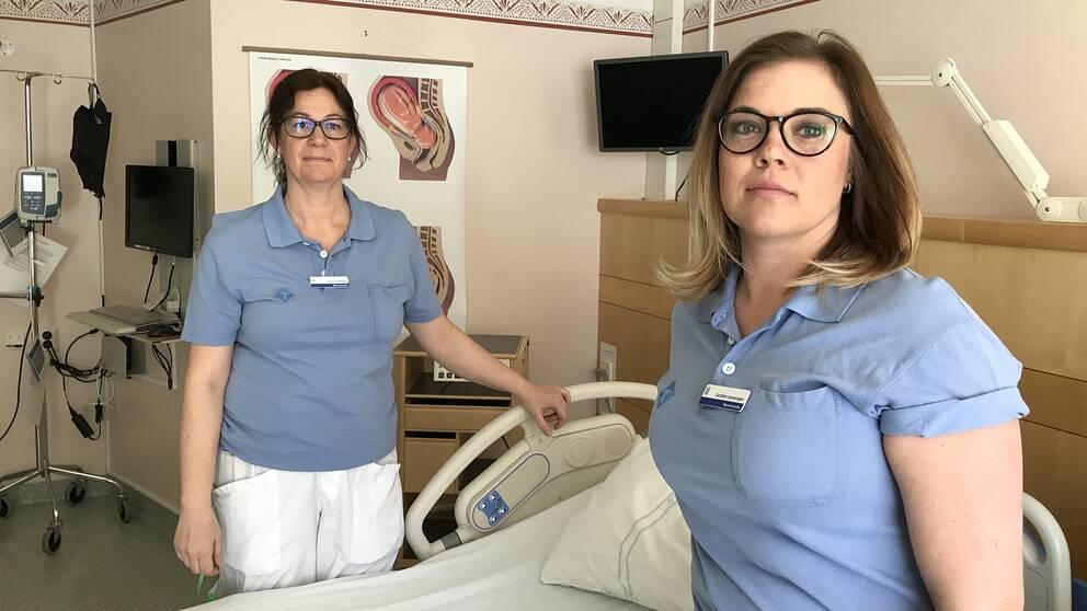 två kvinnor i sjukhuskläder vid patientsäng i sjukhusrum
