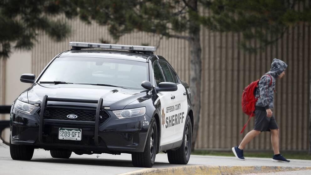 En elev lämnar Columbine High School, som bevakas av polis med anledning av hot.