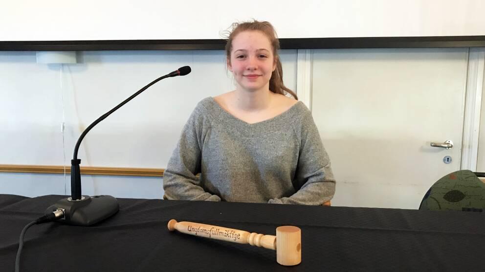 En ung kvinna sitter bakom ett bord med en svart duk. På bordet finns även en domstolsklubba och en mikrofon.