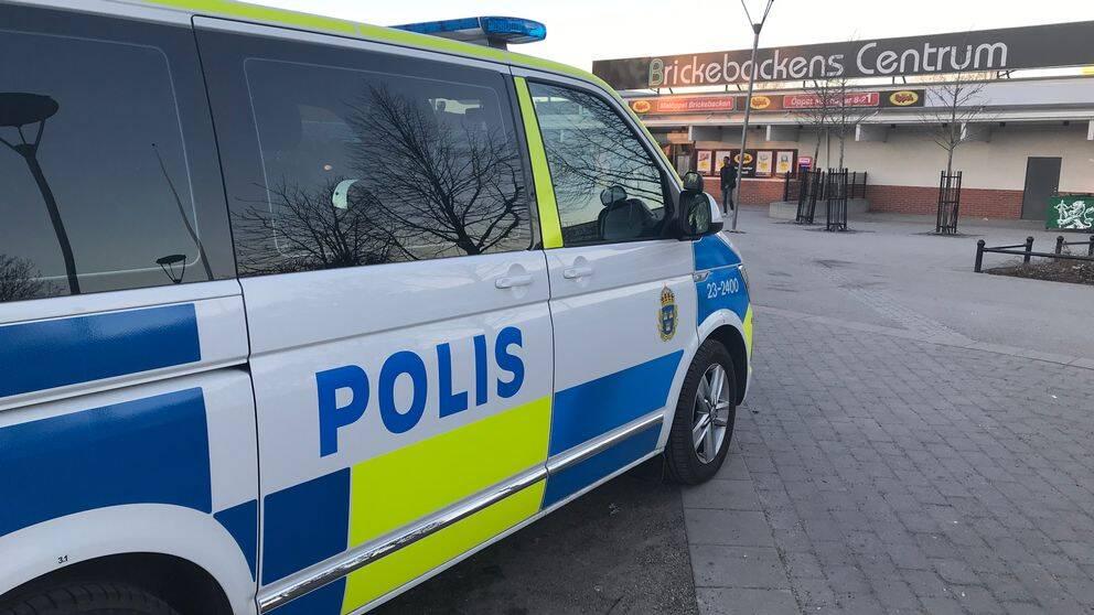En polisbil står parkerad i Birckebackens centrum.