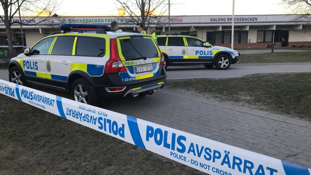 Två polisbilar står i Brickebackens centrum, som är avspärrat efter en skottlossning under onsdagskvällen.